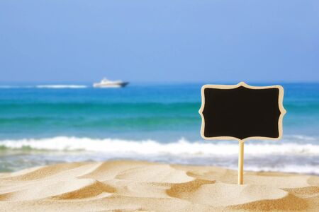 summer sign: Image of tropical sandy beach and blank wooden chalkboard sign. Summer concept Stock Photo
