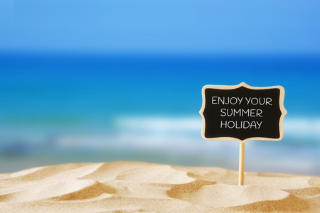 summer sign: Image of tropical sandy beach and blank wooden chalkboard sign with quote: ENJOY YOUR SUMMER HOLIDAY. Summer concept