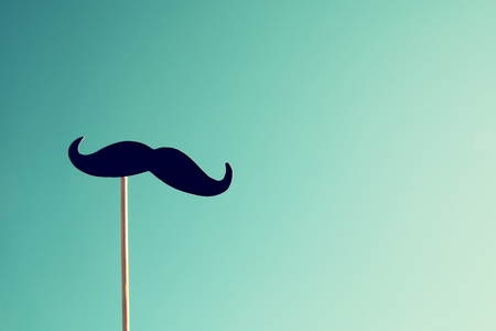 vintage photo: Mustache on stick against the blue sky. retro filtered image Stock Photo