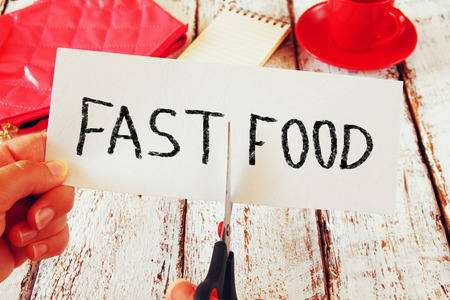 bad behavior: woman hand holding card with the text fast food, cutting the word fast so it written food. healthy food and nutrition concept. retro style