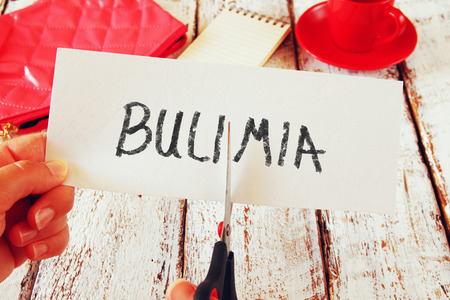 bulimia: woman hand holding card with the text bulimia, cutting the word . healthcare concept. retro style
