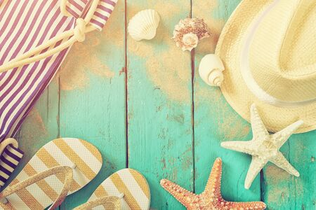 fedora: top view of nautical concept with fedora hat, flip flops and seashells on aqua wooden background