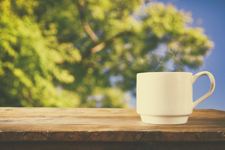 lonliness: Cup of coffee a wooden table in front of tress background. vintage filtered Stock Photo