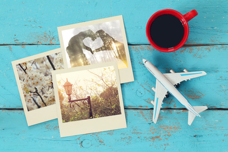 Top view of travel instant photographs next to cup of coffee and airplane over wooden table. traveling concept