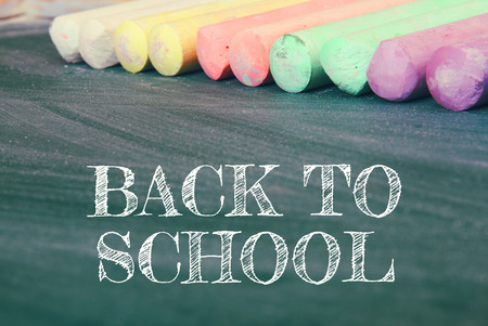 chalks: Top view of blackboard with text: BACK TO SCHOOL, and colorful chalks
