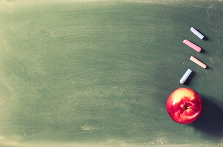 school board: Back to school concept with apple and chlaks on the blackboard
