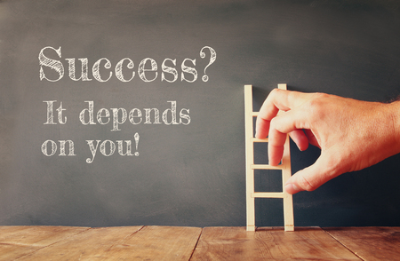 depends: male hand climbing small ladder next to chalkbaoed with the text success it depends on you