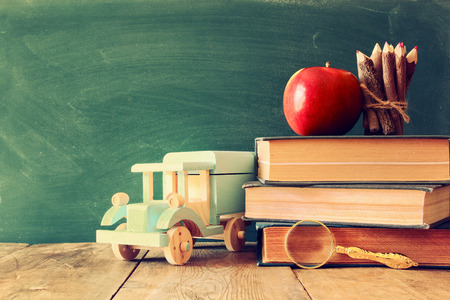 juguetes de madera: Back to school concept. Blackboard with books, wooden pencils and apple on wooden desk. vintage filtered