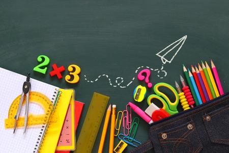 school classroom: Back to school concept. School supplies on empty blackboard.