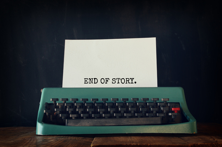 photo story: photo of vintage typewriter with phrase: END OF STORY, on wooden table. vintage filtered