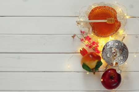 honey apple: Rosh hashanah (jewesh New Year holiday) concept - honey, apple and pomegranate over wooden table. Traditional symbols