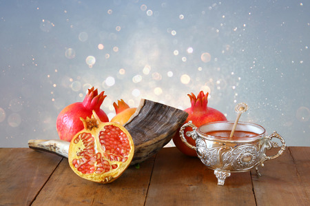 shofar: Rosh hashanah (jewesh New Year holiday) concept - honey, shofar (horn) and pomegranate over wooden table. Traditional symbols Stock Photo