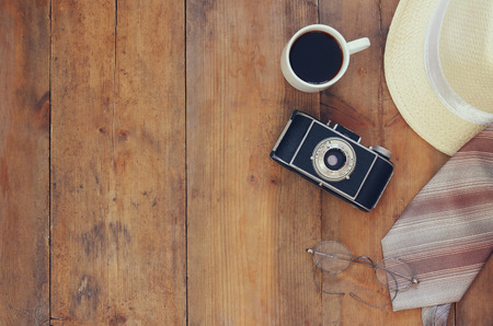 fedora: Vintage camera, glasses, cup of coffee and fedora hat on wooden background. Top view