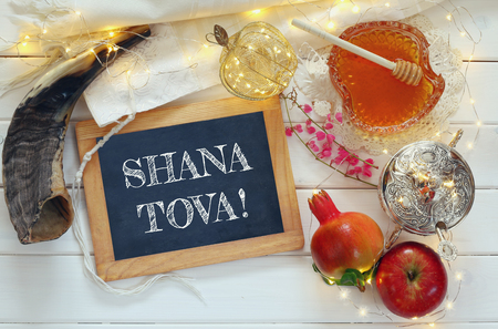 """Rosh hashanah (jewesh New Year holiday) concept - shofar (horn), honey, apple, pomegranate and blackboard with text: """"Happy New Year"""" over wooden table. Traditional symbols Stock Photo"""