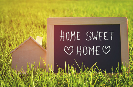 welcome home: chalkboard with the text home sweet home next to wooden small house in the grass
