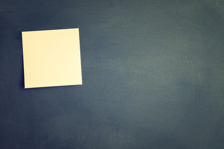 blank note: One blank sticky note attached to blackboard