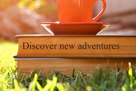 tarde de cafe: La taza de caf� y el libro en la hierba al aire libre, a la hora de la tarde. enfoque selectivo