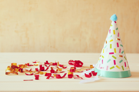 party hat: Party hat next to colorful confetti on wooden table