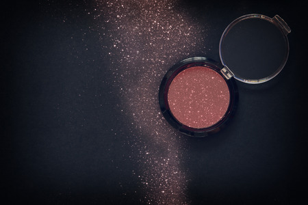 Top view of glitter make up powder dust on black background