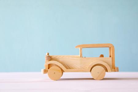 Vintage houten speelgoedauto over houten tafel.