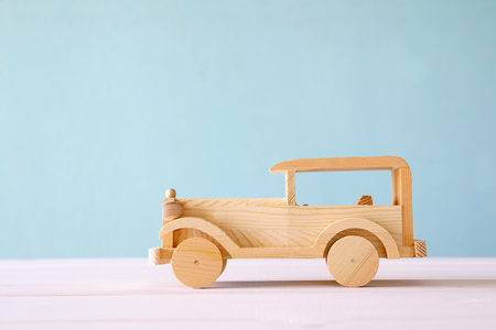 Vintage wooden toy car over wooden table.
