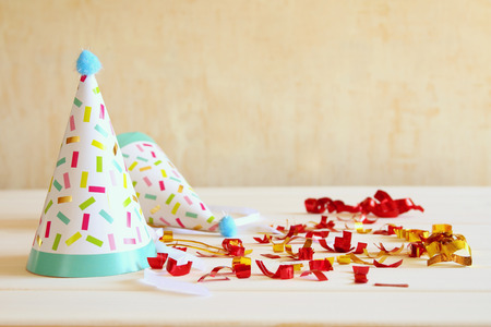 Party hat next to colorful confetti on wooden table. Top view Zdjęcie Seryjne
