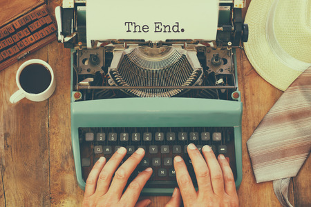 top view  image man hand typing over typewriter with paper sheet and the phrase: THE END. retro filtered