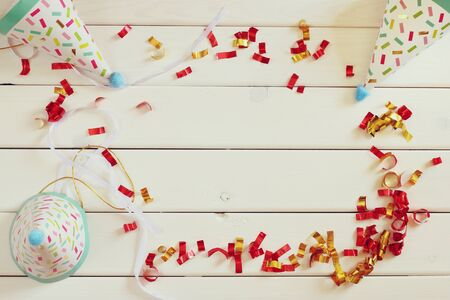 party hat: Party hat next to colorful confetti on wooden table. Top view Stock Photo