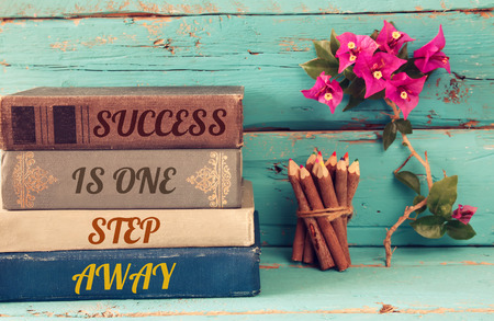 step by step: stack of books over wooden table and motivational phrase - success is one step away.