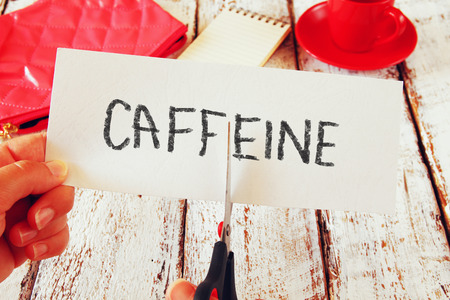 woman hand holding card with the text caffeine, cutting the word. stop or reducing coffee concept. retro style image