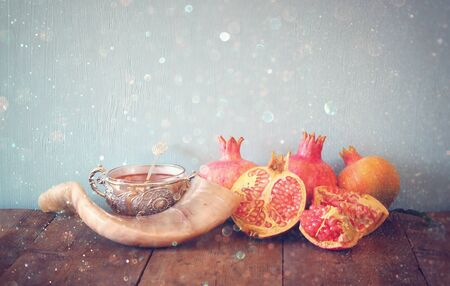 Rosh hashanah (jewesh New Year holiday) concept - shofar (horn) and pomegranates over wooden table. Traditional symbols. Glitter overlay Stock Photo