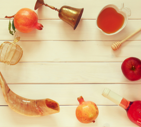 shofar: Rosh hashanah (jewish New Year holiday) concept - shofar (horn), honey, apple and pomegranate over wooden table. Traditional symbols. Vintage filtered Stock Photo
