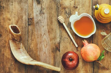 Rosh hashanah (jewish New Year holiday) concept - shofar (horn), honey, apple and pomegranate over wooden table. Traditional symbols Stock Photo