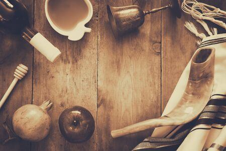 Rosh hashanah (jewish New Year holiday) concept - shofar (horn), honey, apple and pomegranate over wooden table. Traditional symbols. Sepia style photo