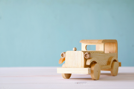 nostalgia: Vintage wooden toy car over wooden table. Nostalgia and simplicity concept. Vintage style image Stock Photo