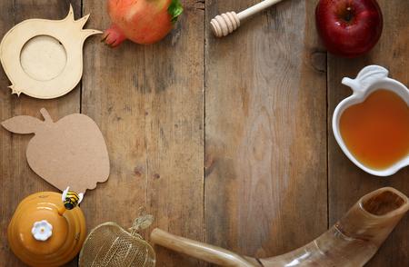 honey apple: Rosh hashanah (jewish New Year holiday) concept - shofar (horn), honey, apple and pomegranate over wooden table. Traditional symbols Stock Photo