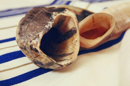 yom kipur: White Prayer Shawl - Tallit, and Shofar (horn). Jewish religious symbols.