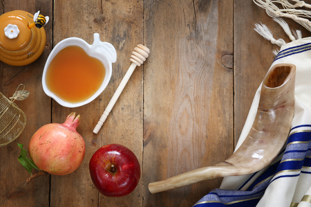 honey apple: Rosh hashanah (jewish New Year holiday) concept - shofar (horn), honey, apple and pomegranate over wooden table. Traditional symbols Stock Photo
