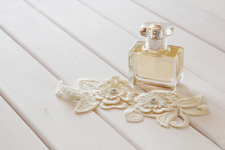 toilette: White pearls necklace and perfume bottle on white toilette table. Selective focus Stock Photo