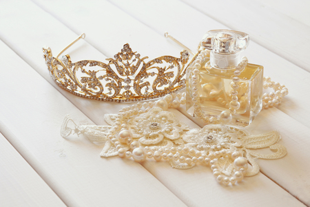 diamond necklace: White pearls necklace, diamond tiara and perfume bottle on white toilette table. Selective focus