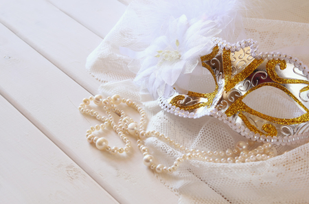 toilette: Vintage white venetian mask and pearls on toilette table.