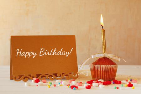 tortas de cumpleaños: concepto de cumpleaños con la magdalena y de la vela junto a la tarjeta de felicitación en mesa de madera