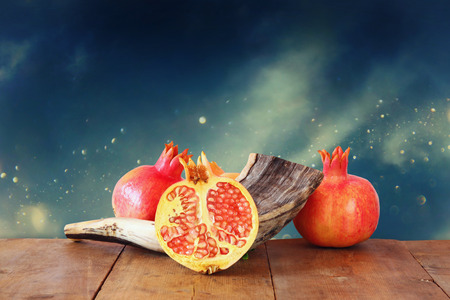 Rosh hashanah (jewish New Year holiday) concept - shofar (horn) and pomegranate over wooden table. Traditional symbols
