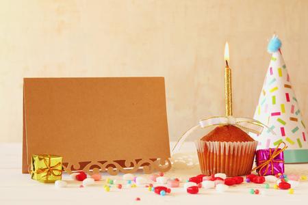 Concepto de cumpleaños con la magdalena y de la vela junto a la tarjeta de felicitación en mesa de madera Foto de archivo - 59725875
