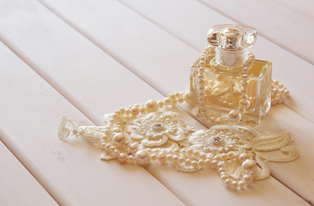 neckless: White pearls necklace and perfume bottle on white toilette table. Selective focus Stock Photo