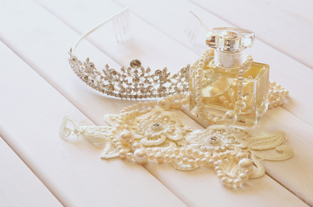 toilette: White pearls necklace, diamond tiara and perfume bottle on white toilette table. Selective focus