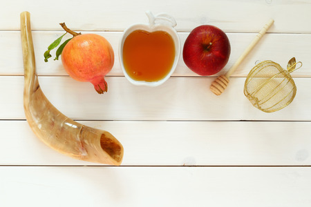 Rosh hashanah (jewish New Year holiday) concept - shofar (horn), honey, apple and pomegranate over wooden table. Traditional symbols