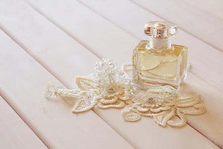 toilette: Perfume bottle and crystal necklace on white toilette table. Selective focus
