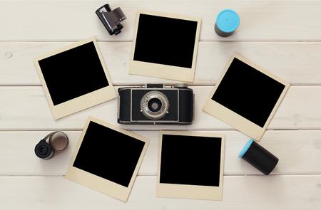 Bovenaanzicht van lege onmiddellijke foto's naast de oude camera en film rollen over houten tafel. Klaar om foto's te zetten