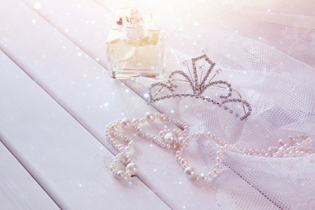 diamond necklace: White pearls necklace, diamond tiara and perfume bottle on toilette table. Selective focus